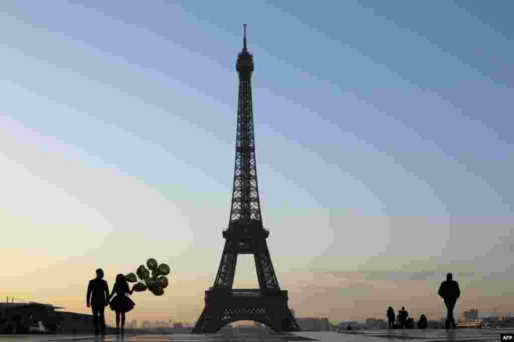 Tourists and a young married couple are pictured at sunrise on the Esplanade du Trocadero near the Eiffel Tower in Paris, France.