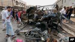 Civilians gather at the scene of a car bomb attack in Kamaliyah neighborhood, a predominantly Shiite area of eastern Baghdad, Iraq, Monday, May 20, 2013.