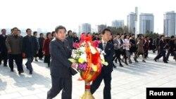 Kuzey Koreliler ülkenin kurucusu Kim il-Sung ve ikinci lideri oğlu Kim Jong-il'in heykellerine çelenk koyarken