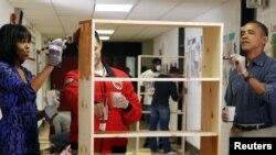 """Presiden Obama dan ibu negara, Michelle Obama berpartisipasi dalam """"Hari Pelayanan Nasional AS 2013"""" dengan mengecat sebuah lemari di Sekolah Dasar Burrville, Washington (19/1)."""