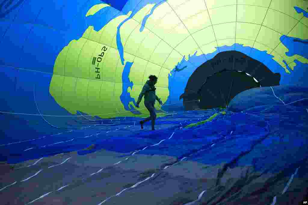 An environmental activist walks inside a hot air balloon before launching it during a demonstration outside of an EU summit in Brussels.