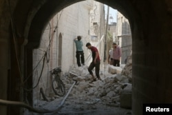 Residents inspect their damaged homes after an airstrike on rebel-held Old Aleppo, Syria, Aug. 15, 2016.