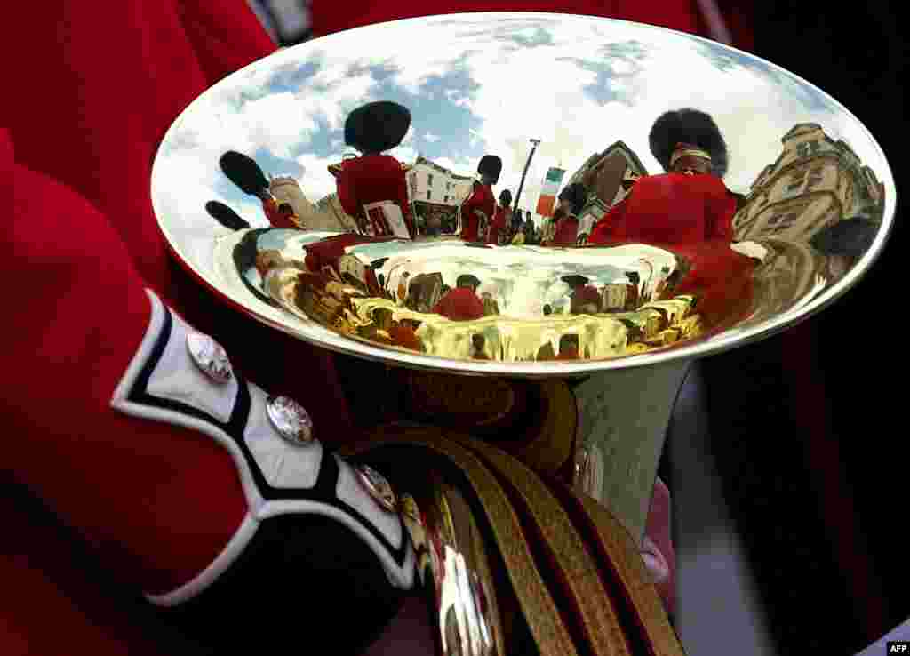 Members of the Band of the Irish Guards are reflected in an brass instrument during the Welcome Ceremony of the Irish President Michael D. Higgins in the town of Windsor, west of London.