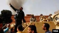 Seorang demonstran yang turun ke jalanan, Senin (1/31) naik ke atas tank tentara Mesir.