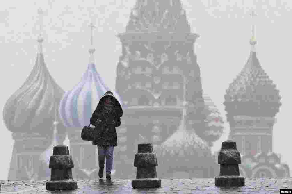 Seorang perempuan berjalan di Lapangan Merah saat hujan salju di Moskow, Rusia.