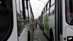 FILE - A police officer guards parked buses used in a new public transportation system in Santiago, March 27, 2007.