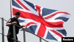 英国皇家海军海神之子两栖登陆舰抵达日本东京一个港口时一名英国水手站在英国国旗前。(2018年8月3日)