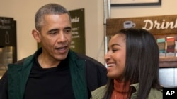 FILE - President Barack Obama and his daughter Sasha prepare to place orders at Pleasant Pops, a market and cafe in Washington, Nov. 28, 2015.