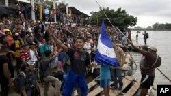 Cientos de migrantes hondureños se reúnen a la orilla del río Suchiate en la frontera entre Guatemala y México, en Tecún Umán, Guatemala, el jueves 18 de octubre de 2018.