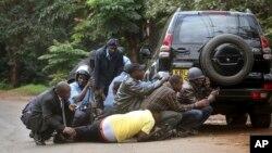 Petugas keamanan dan wartawan berlindung di belakang sebuah mobil, setelah terjadi baku tembak di komplek 'Westgate Mall' di Nairobi Kenya (23/9).
