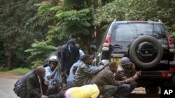 Membros das forças de segurança e jornalistas escondem-se atras de um veiculo durante troca de tiros no centro comercial Westgate (Nairobi, Setembro 2013)