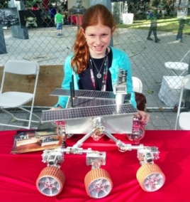Genevieve Beatty, 11, stands in front of the Mars model robot she made with her sister Camille and her father, Robert. (VOA/A. Phillips)