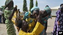 Anggota keluarga meluapkan kegembiraan mereka dengan merangkul kerabat mereka yang merupakan salah satu anak sekolah yang diculik, di Abuja, Nigeria, 20 Mei 2017. (Foto: dok). Ke-82 anak sekolah Nigeria yang baru-baru ini dilepaskan setelah lebih dari tiga tahun diculik oleh Boko Haram.