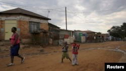 Children play below illegally connected electrical wires in Kliptown, Soweto on Nov. 19, 2014. (REUTERS/Siphiwe Sibeko)