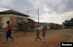 FILE - Children play below illegally connected electrical wires in Kliptown, Soweto. The horrors of 1976 seem distant for today's children.