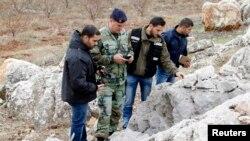 Nhân viên quân đội Libăng kiểm tra phần còn lại cvỏ đạn rocket bắn từ Libăng qua Israel, ngày 29/12/2013.