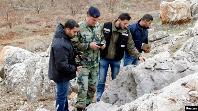 A Lebanese army personnel inspects the remains of a shell that was launched from Lebanon to Israel, which according to activists landed 500m from the Lebanese-Israeli border, in the southern Lebanese village of Sarada,  Dec. 29, 2013.