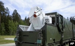 In this video grab provided by RU-RTR Russian television via AP television, March 1, 2018, a Russian military truck with a laser weapon mounted on it is shown at an undisclosed location in Russia. President Vladimir Putin declared Thursday that Russia has developed a range of new nuclear weapons, claiming they can't be intercepted by the enemy.