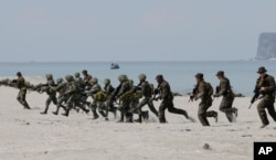 FILE - U.S. and Philippine marines storm the beach to simulate a raid during the joint U.S.-Philippines military exercise at the Naval Training Exercise Command, a former US naval base, and facing the South China Sea at San Antonio township, Zambales province, Philippines.