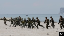 FILE - U.S. and Philippine marines storm the beach to simulate a raid during the joint U.S.-Philippines military exercise at the Naval Training Exercise Command in Zambales province, northwest of Manila, May 9, 2014.