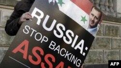 Протестующий держит плакат: «Россия, прекрати поддерживать Асада!»