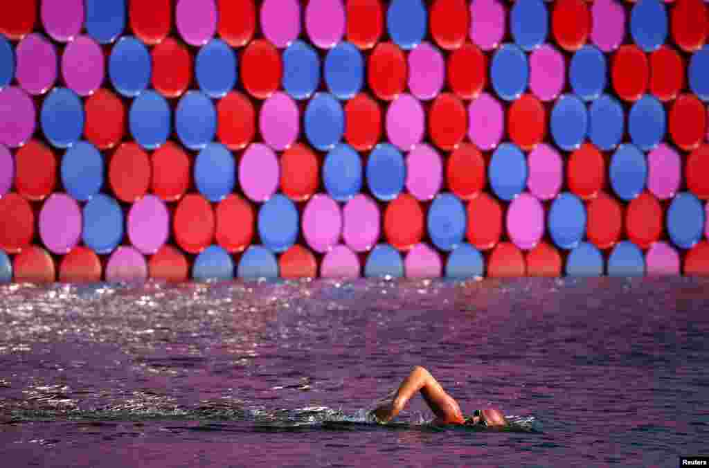 "A man swims past Christo's floating sculpture ""The London Mastaba"" on the Serpentine in London, Britain."