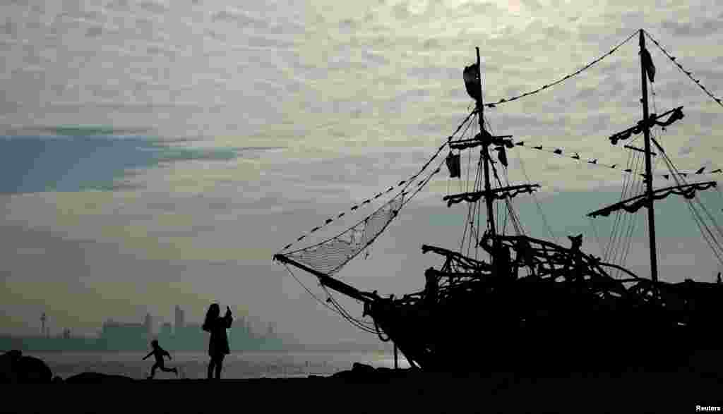 People play in front of a driftwood pirate ship on New Brighton beach near Wallasey, Britain.