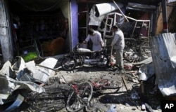 FILE - Men look at the remains of their properties at the site of a suicide attack in Kabul, Afghanistan, July 24, 2017.