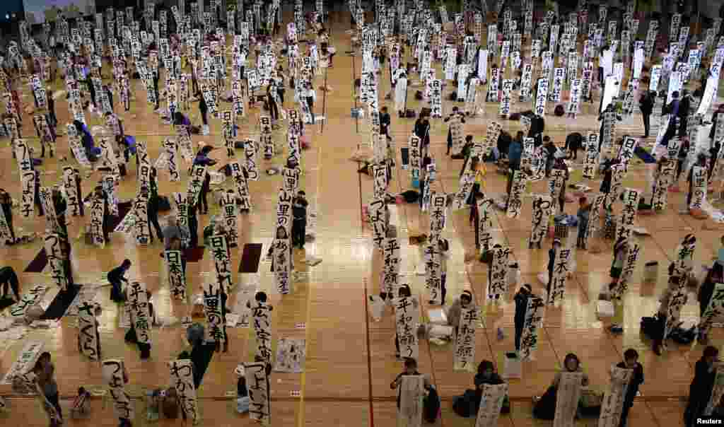 Participants show off their writing at a New Year calligraphy contest in Tokyo, Japan.