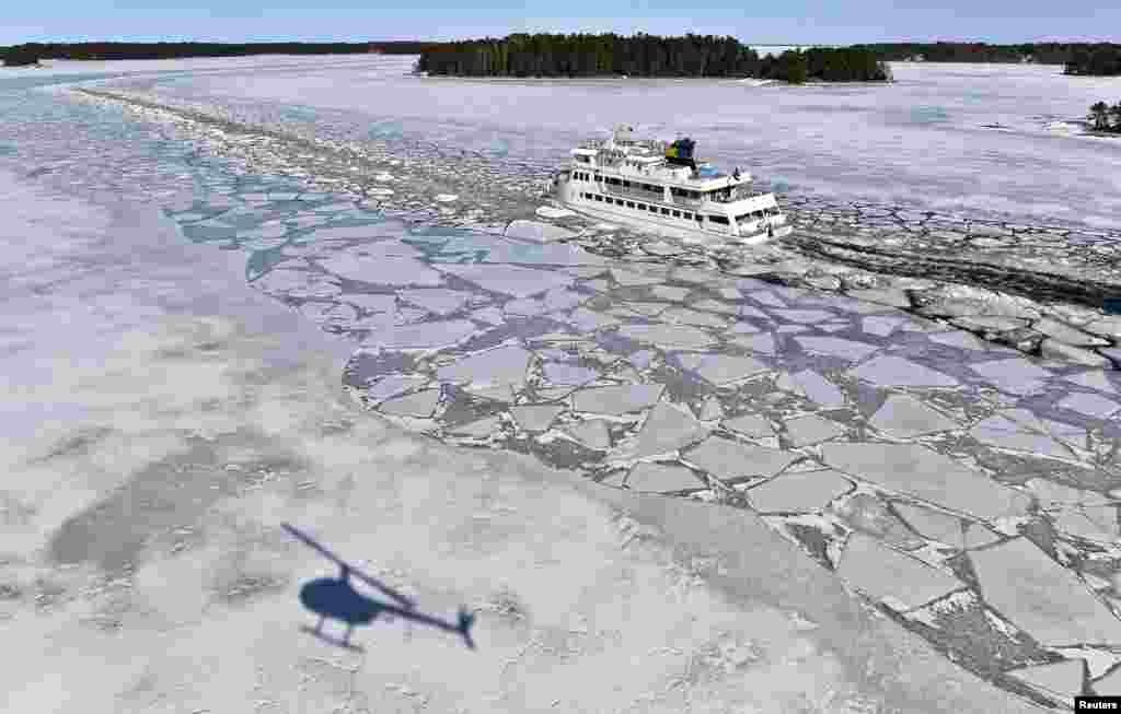 A helicopter casts a shadow on the ice as the passenger ship 'Soderarm' heads in a channel through the ice made by an icebreaker for the daily tour to the island of Husaro in the Stockholm archipelago in Sweden.