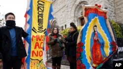 "Maro Park, left, of Fairfax, Virginia, holds a sign saying ""Congress Must Act Now,"" next to Paola Marquez and LaRia Land, both of Silver Spring, Maryland, as they stand by a banner of the Lady of Guadalupe, during a march with others in support of the Deferred Action for Childhood Arrivals (DACA) program, on Capitol Hill, Dec. 12, 2017, in Washington."