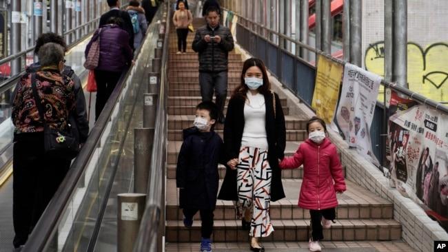 戴着口罩的香港市民在金融区一带行走。(2020年2月19日)