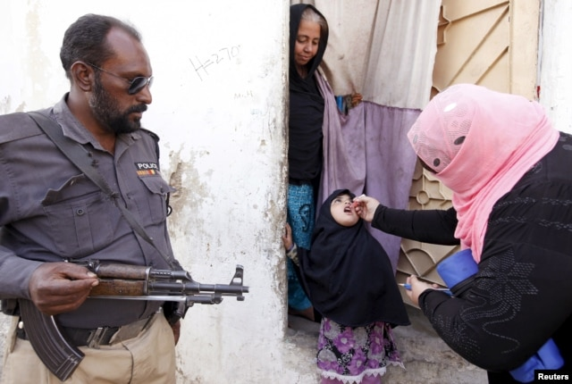 A girl receives polio vaccine drops at the door step of her family home in Karachi, Pakistan, Feb. 15, 2016.