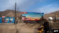 """2018年3月2日,青海铜仁高速公路旁,一名骑摩托车的人驶过宣传牌,牌上有中国国家主席习近平像和中文藏文标语""""人民对美好生活的向往,就是我们的奋斗目标""""。"""