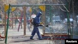 មន្ត្រីសុខាភិបាលម្នាក់ស្ថិតក្នុងសម្លៀកបំពាក់តាមក្បួនវេជ្ជសាស្ត្រ ដើរបាញ់ថ្នាំសម្លាប់មេរោគនៅកន្លែងក្មេងលេងកម្សាន្ត ដើម្បីទប់ទល់នឹងការឆ្លងរាលដាលនៃវីរុសកូវីដ១៩ នៅទីក្រុង Almaty ប្រទេសកាហ្សាក់ស្ថាន ថ្ងៃទី២៧ ខែមីនា ឆ្នាំ២០២០។