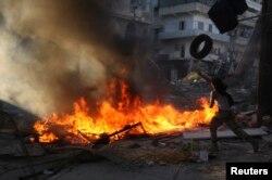 2013年9月25日叙利亚反政府武装人员点燃轮胎和其他物件以躲避政府军狙击手