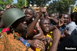 FILE - Anti-government protesters chant slogans in front of army headquarters in Ouagadougou, capital of Burkina Faso, Oct. 31, 2014.
