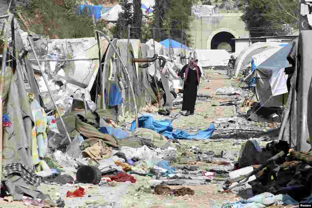A woman inspects damage at a camp for internally displaced people after it was hit by what residents said was shelling carried out by forces allied with the government , near the Syrian-Turkish border in Jabal al-Turkman, Latakia province, Syria, Jan. 31, 2016.
