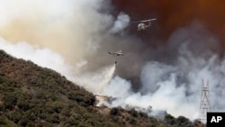 Helicopters drop fire retardant and water over the BlueCut fire in the Cajon Pass near San Bernardino, California, Aug. 17, 2016.