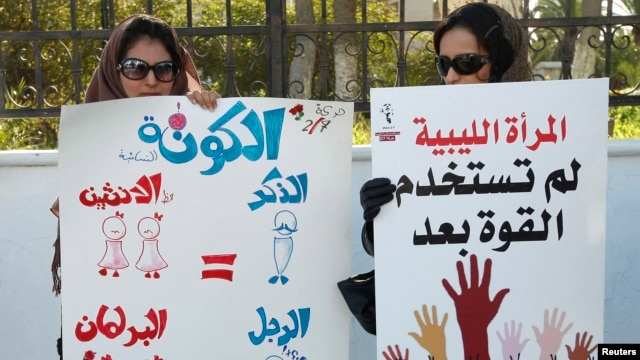 "Women hold banners during a demonstration for women's rights in Tripoli. The poster on the left reads, ""Quota: Since two women equal one man (in Sharia law), there should be two women for every man in parliament. Then the formula will be perfect."" Feb. 7, 2013."