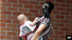 一位北韓婦女背著幼兒進入首爾南部難民安置設施Hanawon Center