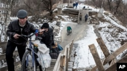 FILE - Local residents walk across a bridge damaged during fighting between Ukrainian government forces and Russia-backed rebels in Stanytsia Luhanska, Luhansk region, eastern Ukraine, Jan. 16, 2016.