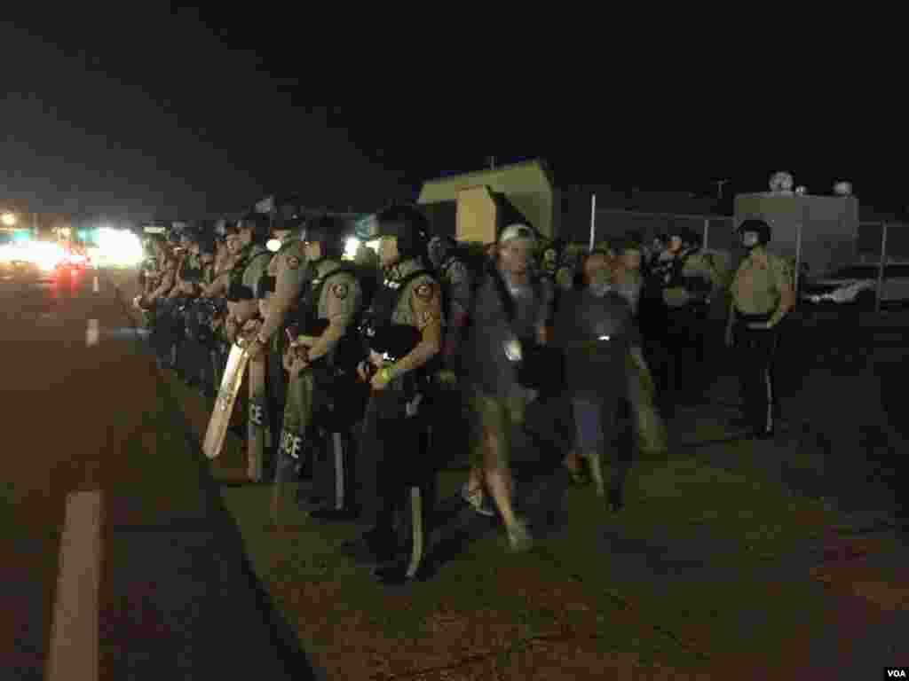 Cảnh sát tăng cường hiện diện trong lúc người biểu tình tụ tập tại Ferguson, Missouri, ngày 10 tháng 8, 2015. (Kane Farabaugh / VOA News)