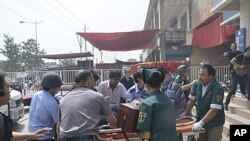 A handout picture shows rescuers carrying an injured victim on a stretcher out of a police station after a clash in Hotian, Xinjiang Uygur Autonomous Region, July 18, 2011