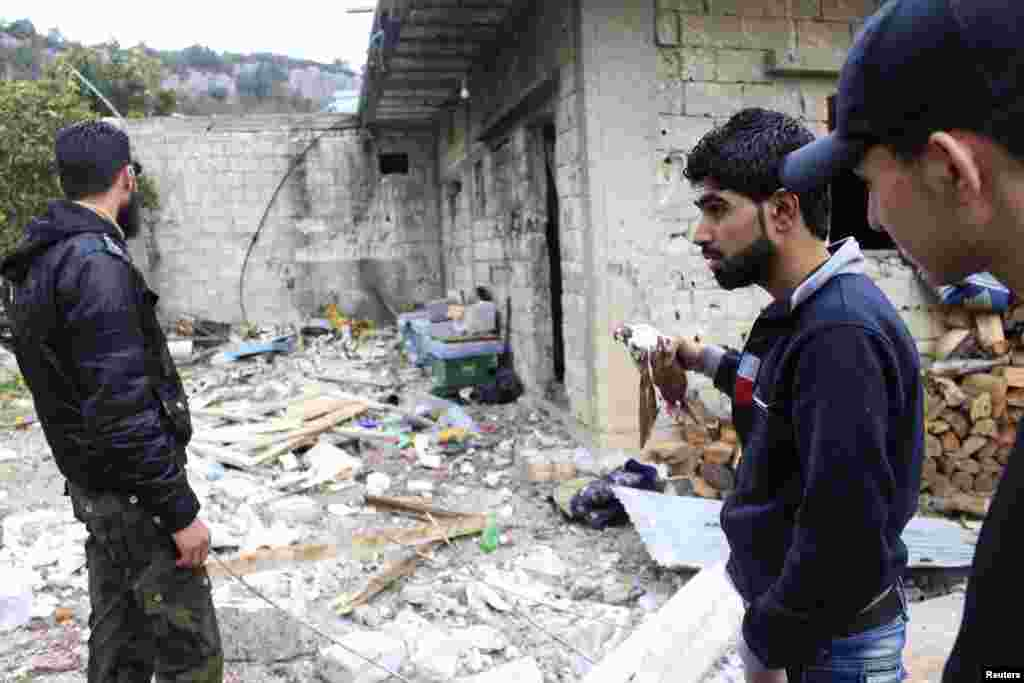 A Free Syrian Army fighter holds a dead bird as his comrades inspect the damage caused by what activists said were barrel bombs dropped by government forces in Jabal al-Akrad, Latakia, Jan. 23, 2014.
