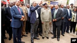 President Uhuru Kenyatta, middle, points as he views the fire damage at the Jomo Kenyatta International Airport, with Inspector General of Police David Kimaiyo, Nairobi, Aug. 7, 2013.