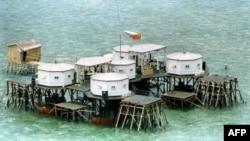 Cờ Trung Quốc và ăng ten đĩa vệ tinh trên một cấu trúc do Trung Quốc xây trên một đảo trong quần đảo Trường Sa