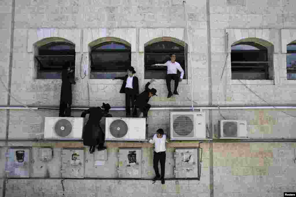 Ultra-Orthodox Jewish boys climb down a wall near the scene of a suspected attack, in Jerusalem, Aug. 4, 2014.