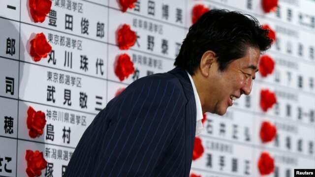 Japan's Prime Minister and leader of the ruling Liberal Democratic Party (LDP) Shinzo Abe smiles as he leaves an election campaign center at the LDP headquarters in Tokyo, July 21, 2013, after an upper house election.