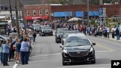People line the street to pay respects as the hearse carrying the body of Rev. Billy Graham travels through Black Mountain, N.C., Feb. 24, 2018. The procession is part of more than a week of mourning that culminates with his burial next week at his library in Charlotte.